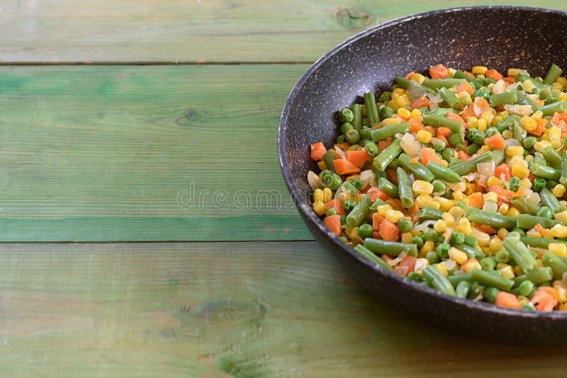 Blandning av grönsaker som stekas i en panna royaltyfri bild