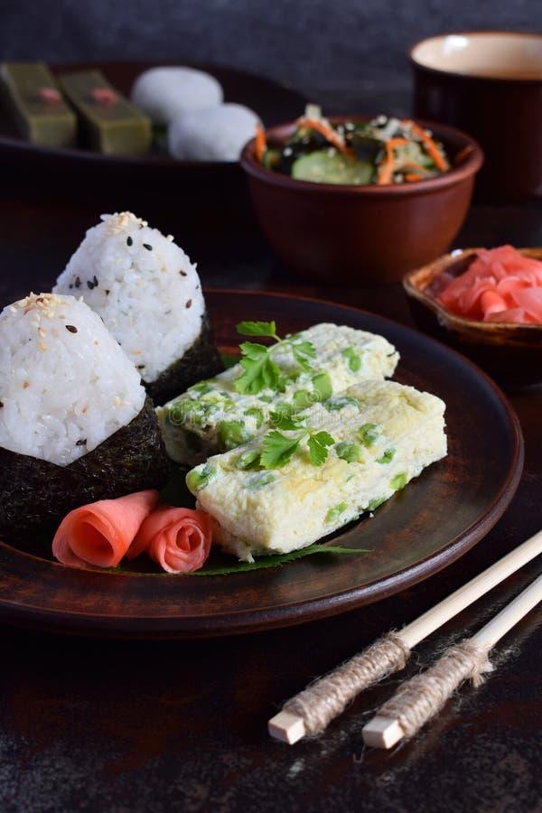 Blandning av japansk mat - ris klumpa ihop sig onigirien, omelett, ingefäran, sallad för sunomonowakamegurka Traditionell efterrä fotografering för bildbyråer