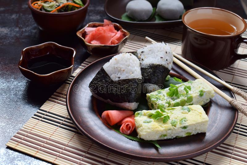 Blandning av japansk mat - ris klumpa ihop sig onigirien, omelett, ingefäran, sallad för sunomonowakamegurka Traditionell efterrä arkivbilder