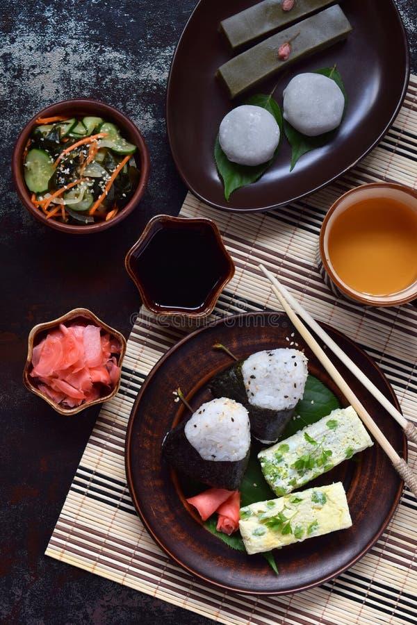 Blandning av japansk mat - ris klumpa ihop sig onigirien, omelett, ingef?ran, sallad f?r sunomonowakamegurka Traditionell efterr? arkivbilder