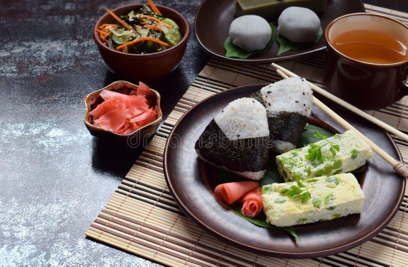 Blandning av japansk mat - ris klumpa ihop sig onigirien, omelett, ingef?ran, sallad f?r sunomonowakamegurka Traditionell efterr? arkivfoto