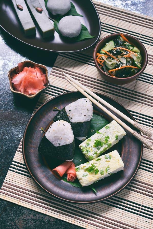 Blandning av japansk mat - ris klumpa ihop sig onigirien, omelett, ingef?ran, sallad f?r sunomonowakamegurka Traditionell efterr? royaltyfri foto
