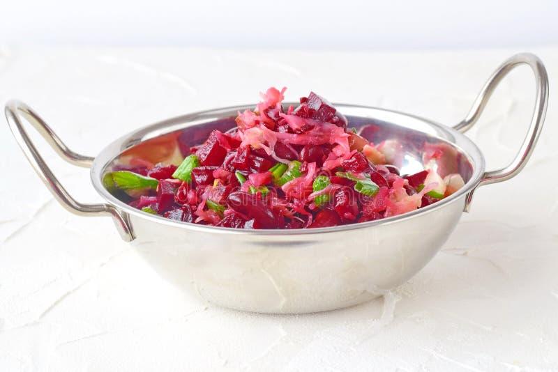 Blandning av kokt rödbeta, bönor, surkålen, knipor och salladslöken med olivolja och vinvinäger i en metallplatta med royaltyfri fotografi