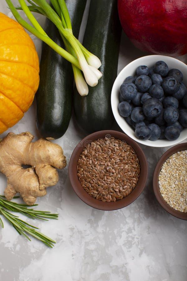 Blandning av nya sunda vegetariska ingredienser av grönsaker, frö, kli, frukt och bär på en grå cementbakgrund royaltyfria bilder