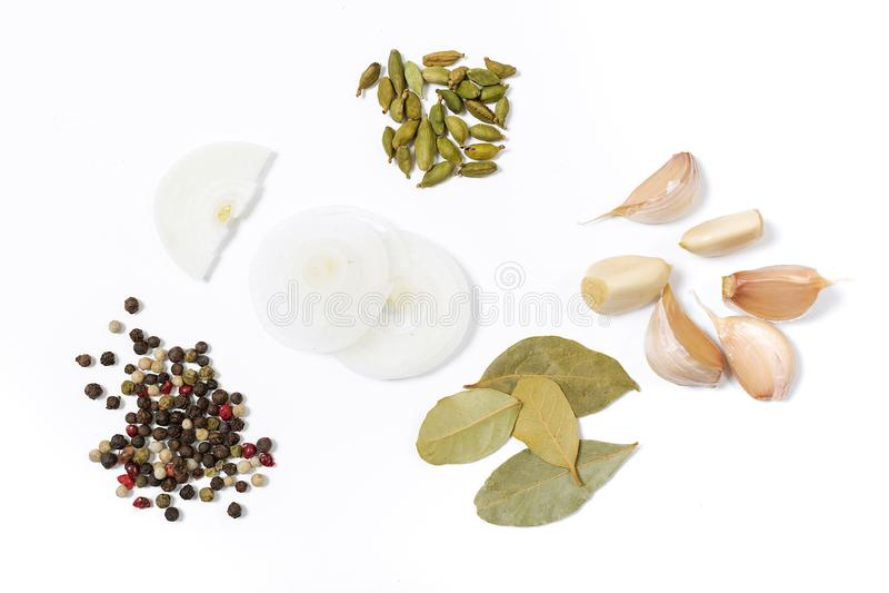Blandning av smaktillsatser från löken, lagerblad, koriander, vitlök, svartpeppar på en vit bakgrund arkivfoto
