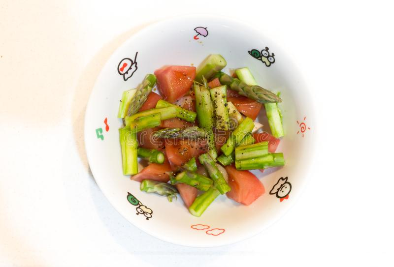 Blandning av tomater, sparris och peppar på en keramisk bunke arkivfoto