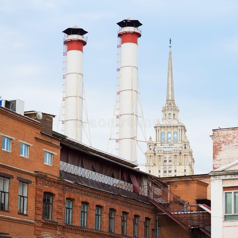 Blandning av två rör och byggnader av olika tider mot himmel Gammal industribyggnad av fabriken från röd tegelsten royaltyfri foto
