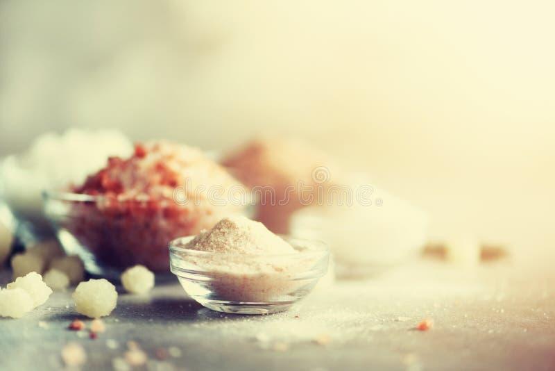 Blandningen av olika salta typer på grå färger hårdnar bakgrund Havet saltar, svart och rosa Himalayan salta kristaller, pulver royaltyfri foto