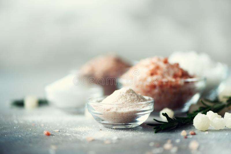 Blandningen av olika salta typer på grå färger hårdnar bakgrund Havet saltar, svart och rosa Himalayan salta kristaller, pulver arkivbild