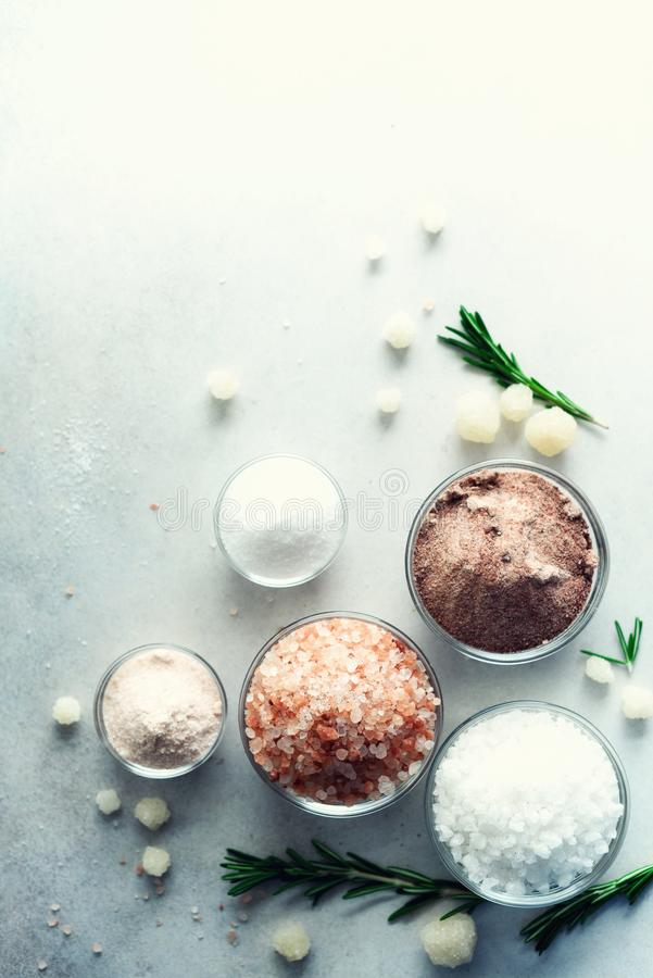Blandningen av olika salta typer på grå färger hårdnar bakgrund Havet saltar, svart och rosa Himalayan salta kristaller, pulver royaltyfria bilder