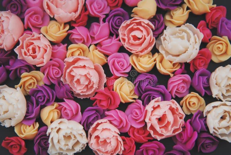 Blandningen av rosa färger och persikan fejkar utrymme för kopian för bakgrund för plast- mini- rosessblommor svart Hantverk kons arkivfoto