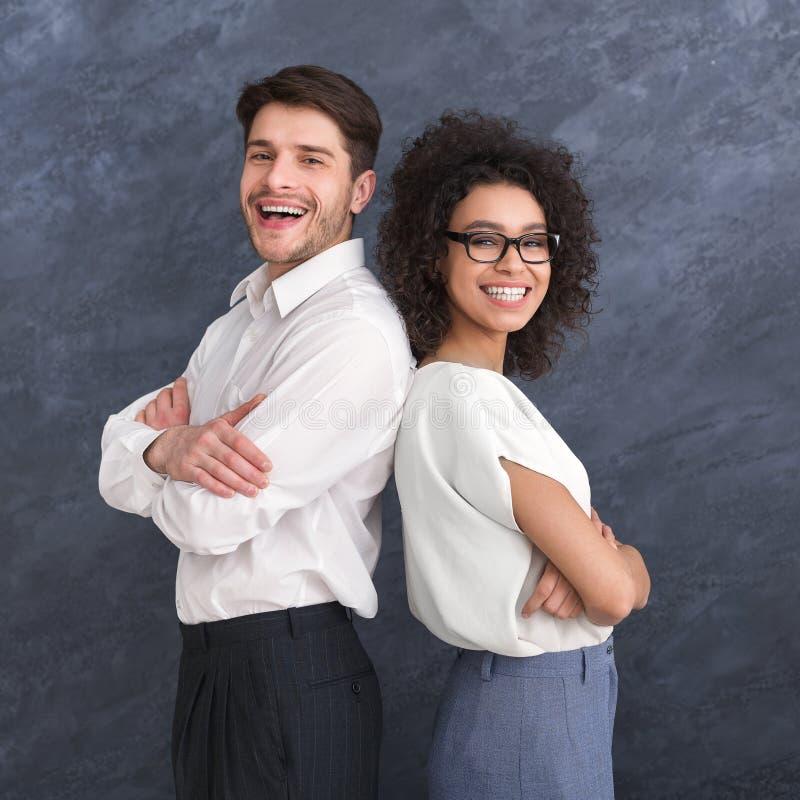 Blandras- affärsman och kvinna mot grå bakgrund royaltyfri bild