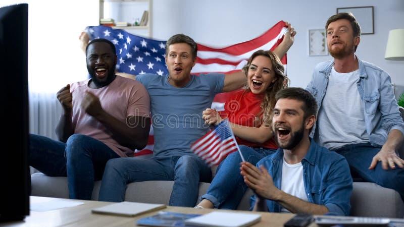 Blandras- amerikanska fans som håller ögonen på matchen på hemmastadd TV och att fira lagmål arkivbilder