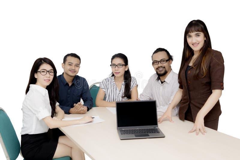 Blandras- arbetare med bärbara datorn på skrivbordet fotografering för bildbyråer