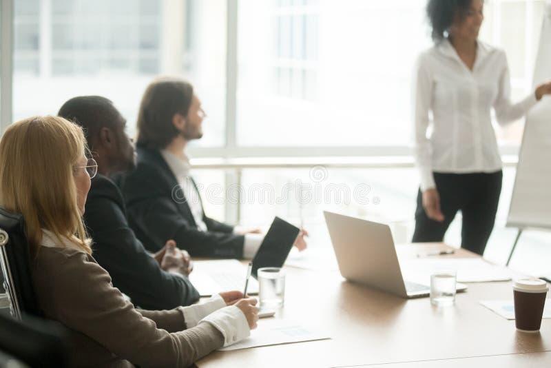 Blandras- businesspeople som deltar i utbildning för företags grupp eller