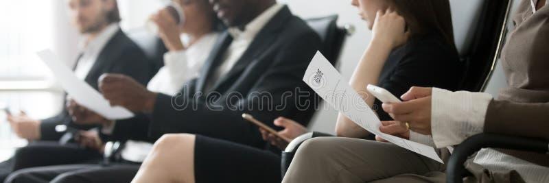 Blandras- folk sidoför horisontalfoto som sitter i väntande intervju för kö royaltyfri fotografi