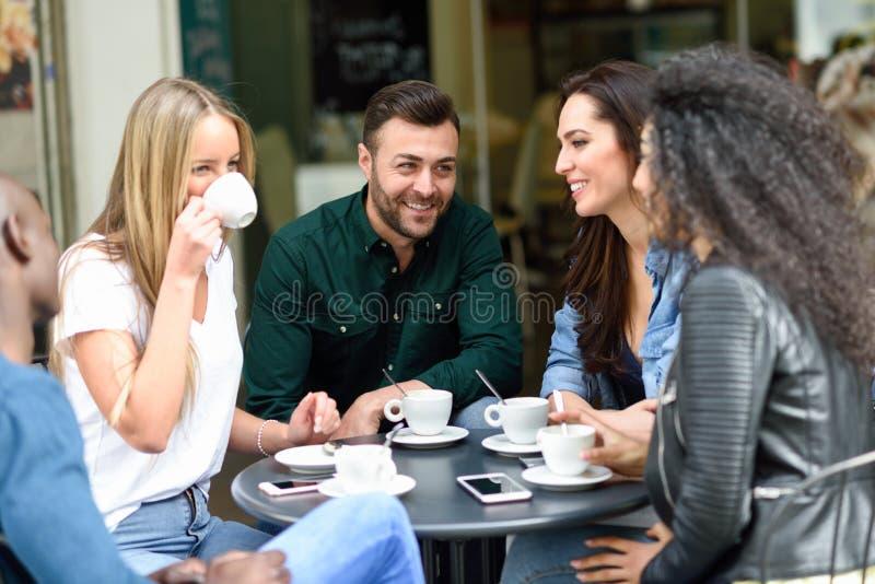 Blandras- grupp av fem vänner som har ett kaffe tillsammans royaltyfria bilder