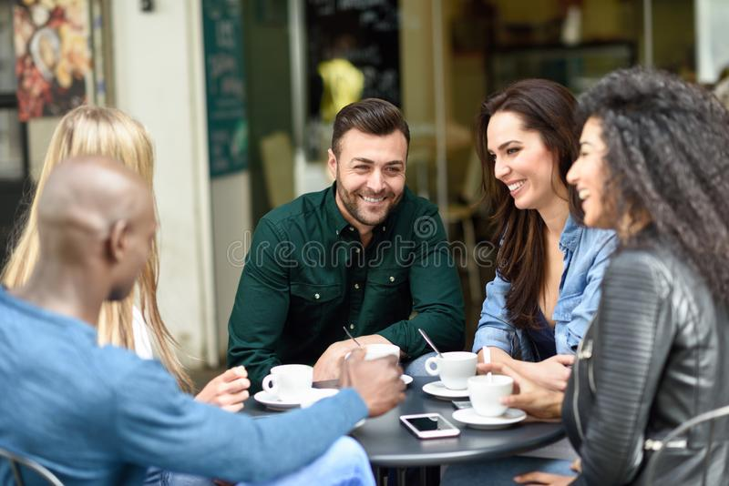 Blandras- grupp av fem v?nner som har ett kaffe tillsammans royaltyfria foton