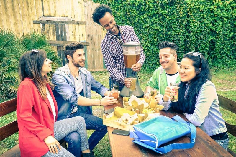 Blandras- grupp av lyckliga vänner som äter och rostar på bbq arkivbild