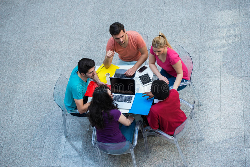 Blandras- grupp av unga studenter som tillsammans studerar Högt vinkelskott av ungdomarsom sitter på tabellen royaltyfri fotografi