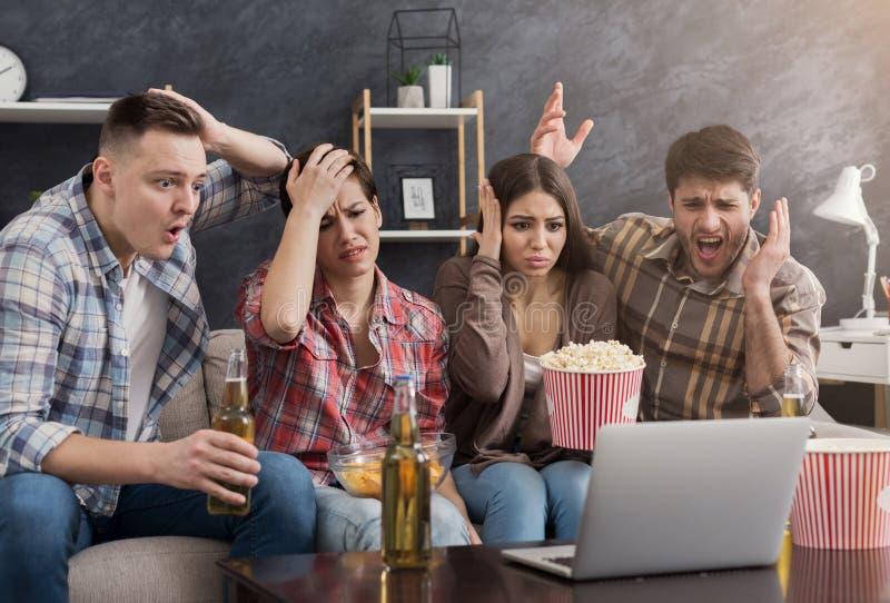 Blandras- grupp av upprivna vänner som håller ögonen på filmen royaltyfria bilder