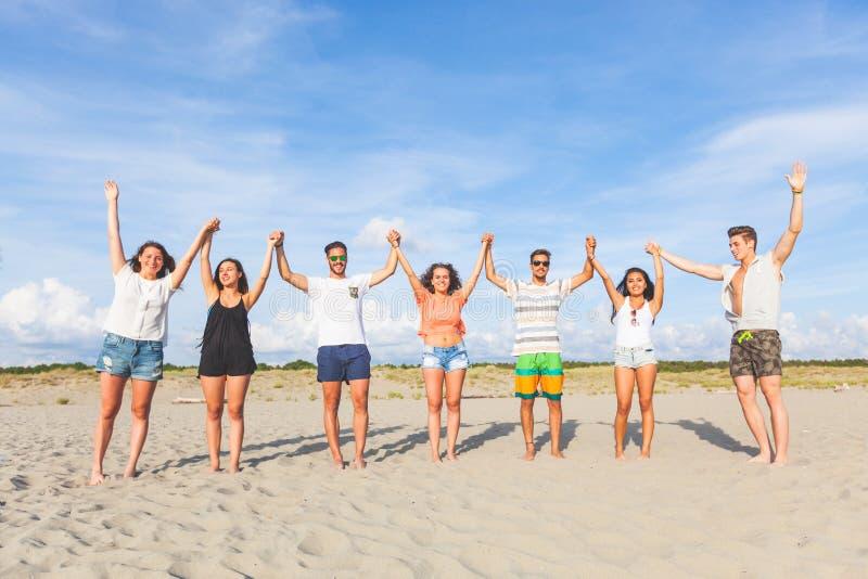 Blandras- grupp av vänner med lyftta händer på stranden royaltyfri fotografi