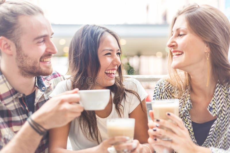 Blandras- grupp av vänner som har ett kaffe tillsammans royaltyfria bilder