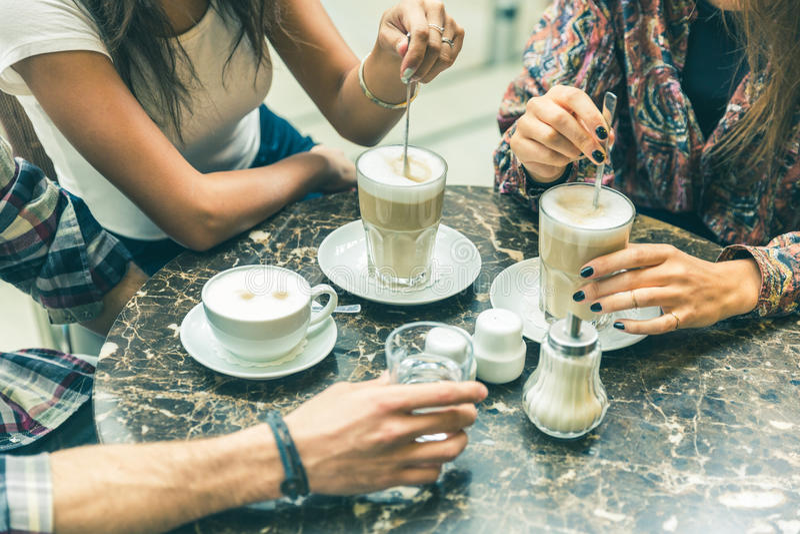 Blandras- grupp av vänner som har ett kaffe tillsammans royaltyfria foton