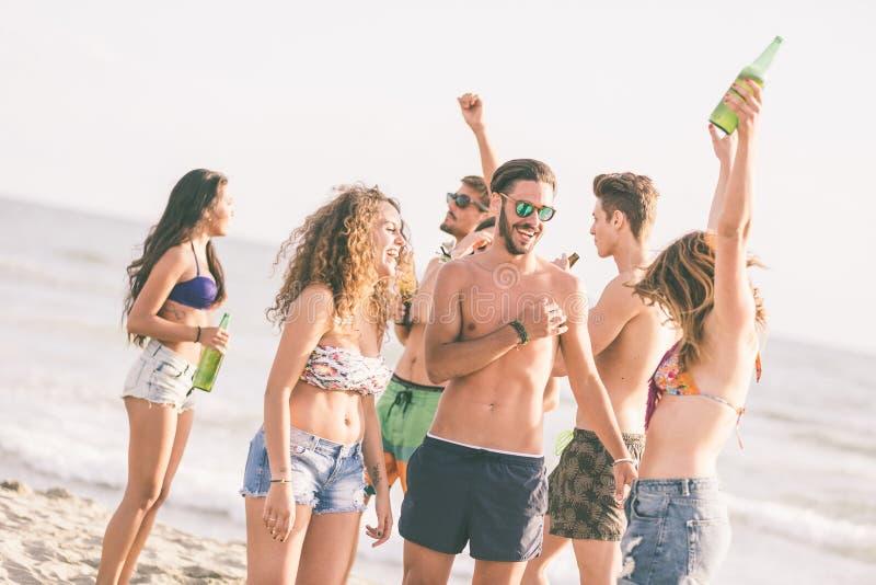 Blandras- grupp av vänner som har ett parti på stranden royaltyfria bilder