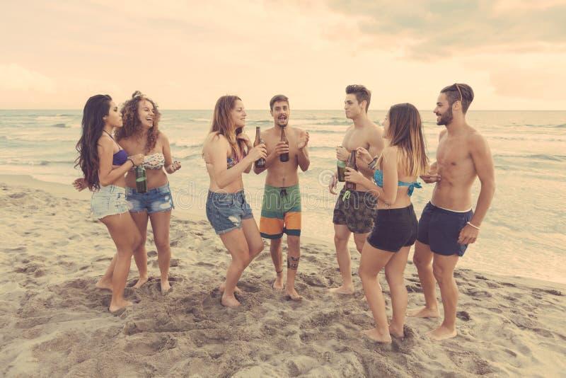 Blandras- grupp av vänner som har ett parti på stranden royaltyfria foton