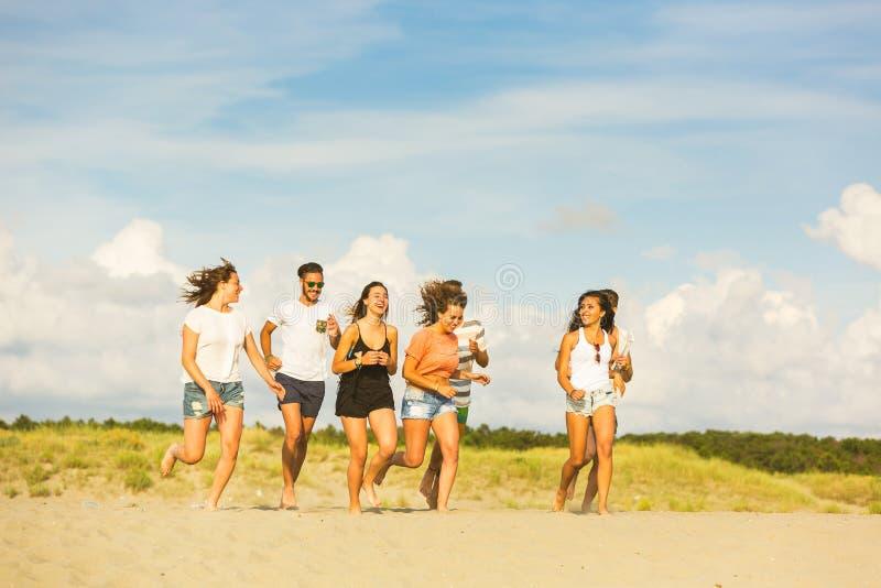 Blandras- grupp av vänner som kör på stranden royaltyfri fotografi