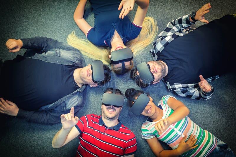 Blandras- grupp av vänner som spelar på inomhus vrexponeringsglas - virtuell verklighetbegrepp med ungdomarsom har gyckel tillsam arkivbild