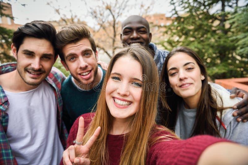 Blandras- grupp av vänner som tar selfie arkivfoton