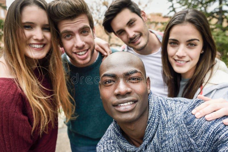 Blandras- grupp av vänner som tar selfie fotografering för bildbyråer