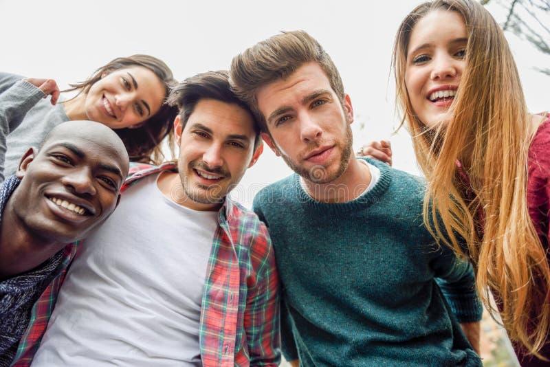Blandras- grupp av vänner som tar selfie royaltyfri bild