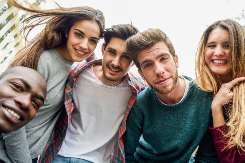 Blandras- grupp av vänner som tar selfie royaltyfria foton