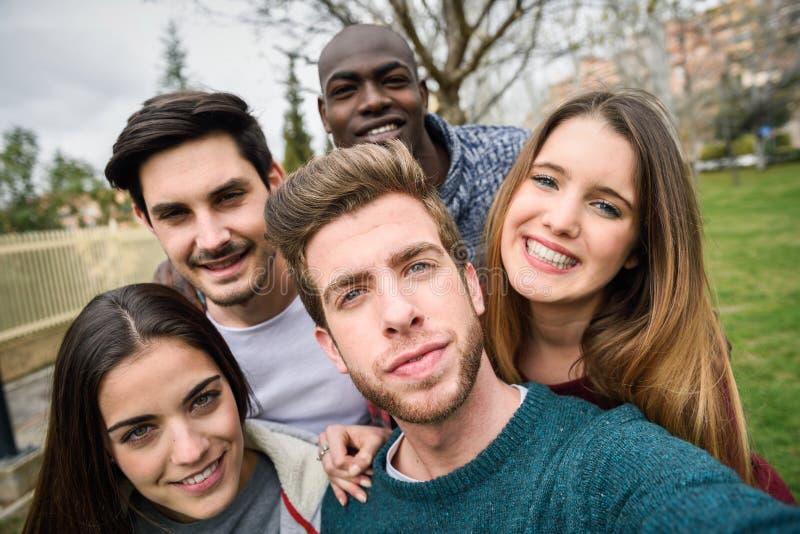 Blandras- grupp av vänner som tar selfie arkivfoto