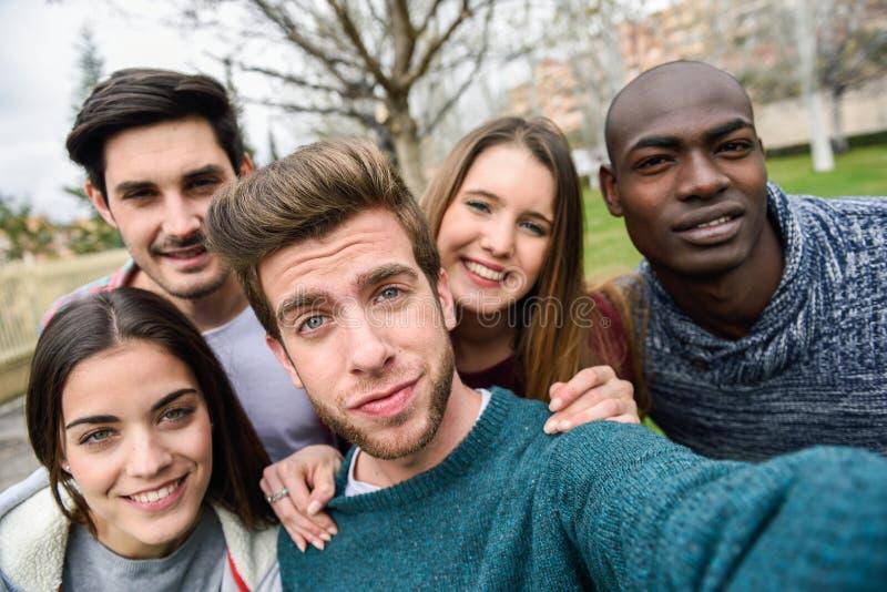 Blandras- grupp av vänner som tar selfie royaltyfria bilder