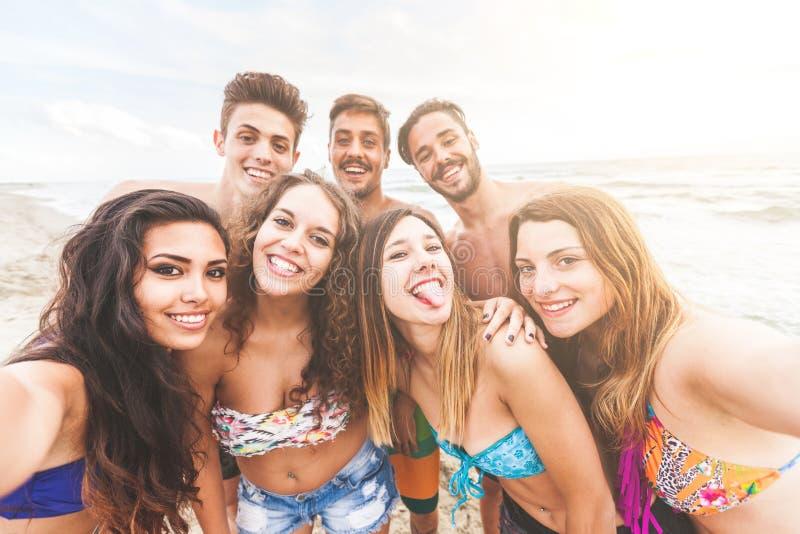 Blandras- grupp av vänner som tar selfie på stranden arkivfoto