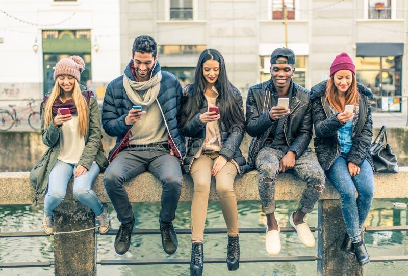 Blandras- grupp människor med mobiltelefoner royaltyfria foton