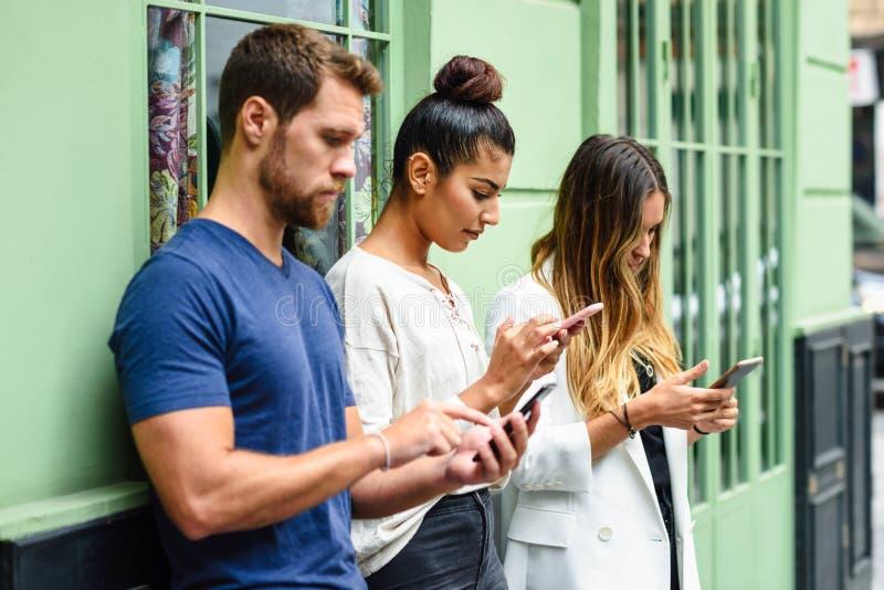 Blandras- grupp människor som ner ser på den smarta telefonen royaltyfria foton