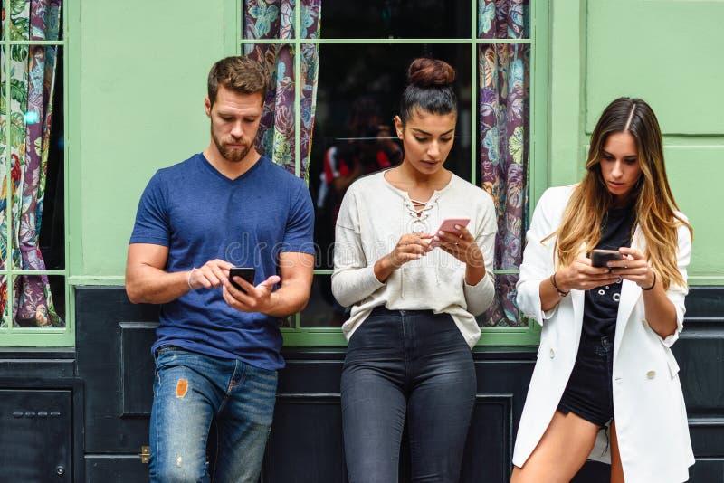 Blandras- grupp människor som ner ser på den smarta telefonen arkivfoto