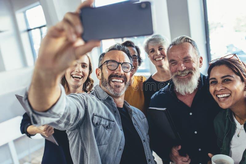 Blandras- grupp människor som tar selfie på kontoret arkivbild