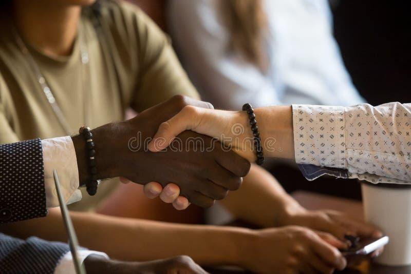 Blandras- handskakninghälsning under affärsmöte i kafé royaltyfri bild