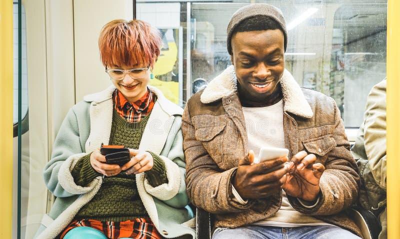 Blandras- hipstervänner kopplar ihop att ha gyckel med telefonen royaltyfria foton