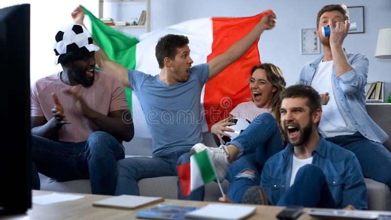 Blandras- italienska vänner som sitter på soffan och den hållande ögonen på leken som firar mål royaltyfri fotografi