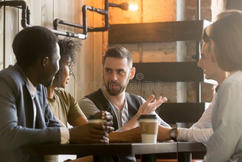 Blandras- kollegor som diskuterar idéer under arbetsavbrott i caf royaltyfri bild