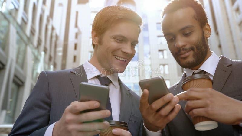 Blandras- kollegor som ser foto på kaffeavbrottet genom att använda smartphoneapps royaltyfria foton