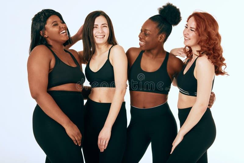 Blandras- kvinnlig med den olika format- och etnicitetst?llningen tillsammans och leende fotografering för bildbyråer