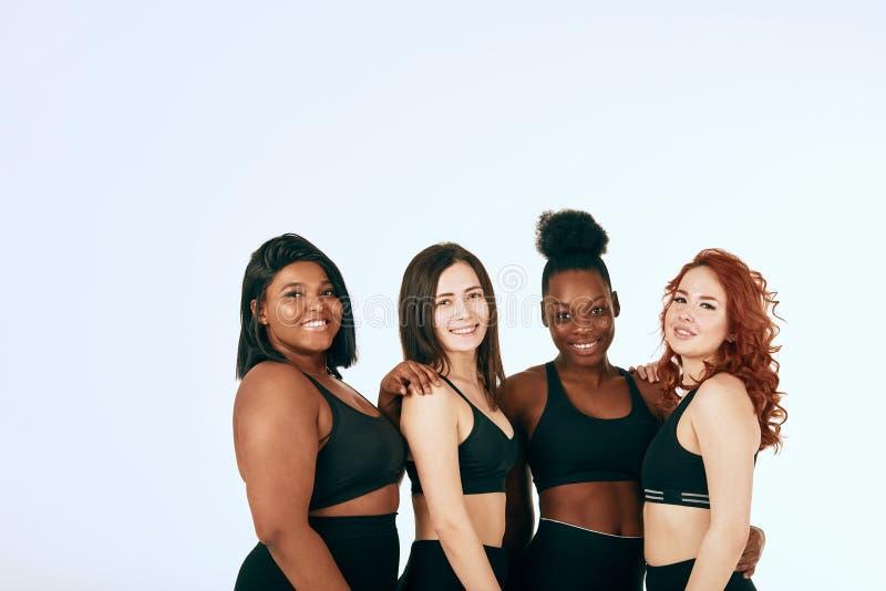 Blandras- kvinnlig med den olika format- och etnicitetst?llningen tillsammans och leende arkivbild
